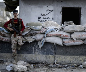 A fighter of Syrian opposition stands at a checkpoint in northwestern city of Idlib, Syria, late Saturday, Oct. 13, 2018