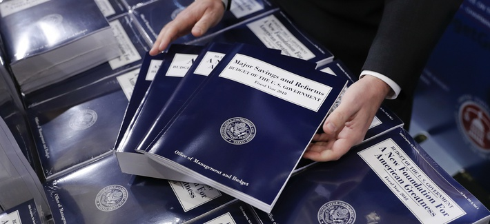 Eric Ueland, Republican staff director, Senate Budget Committee, lays out a copy of President Donald Trump's fiscal 2018 federal budget, before distributing them to congressional staffers, Tuesday, May 23, 2017, on Capitol Hill in Washington.
