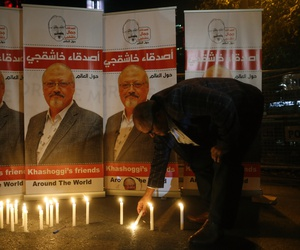 An activist lights a candle during a candlelight vigil for Saudi journalist Jamal Khashoggi outside Saudi Arabia's consulate in Istanbul, Thursday, Oct. 25, 2018.