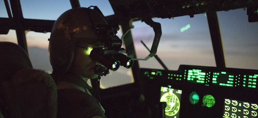 A C-130J pilot wears night vision goggle during a training mission above Yokota Air Base, Japan.