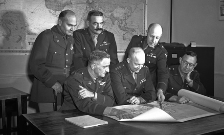 These six U.S. generals, who are directing the operations of U.S. forces from Great Britain check over a map during a conference on August 19, 1942.