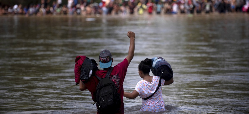 A migrant raises his fist as he nears the Mexican side of the the Suchiate River, that connects Guatemala and Mexico, Monday, Oct. 29, 2018.