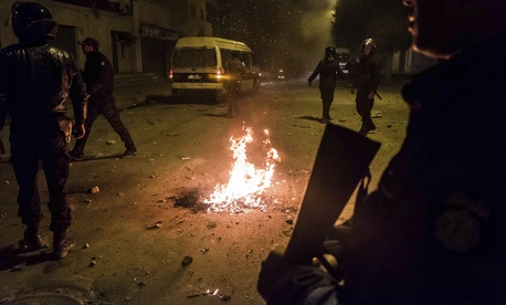 Riot police patrol in the streets of Tebourba, south of the Tunisian capital, Tunis, during anti-government protests, Tuesday, Jan. 9, 2018.