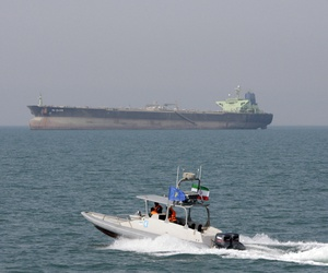 In this July 2, 2012 file photo, an Iranian Revolutionary Guard speedboat moves in the Persian Gulf while an oil tanker is seen in background.