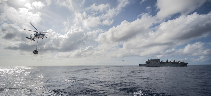 Military Sealift Command fleet replenishment oiler USNS John Ericsson (T-AO 194) and MH-60S Seahawk helicopters from the Island Knights of Helicopter Sea Combat Squadron (HSC) 25 participate in an exercise in the South China Sea, Oct. 20, 2014.