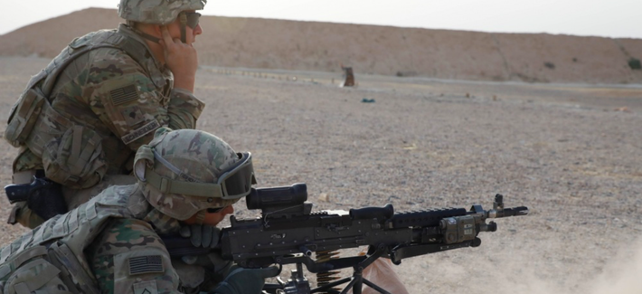 U.S. Army Spc. Matthew Schneider, assigned to Bandit Troop, 3rd Calvary Regiment, observes Pfc. Ryan Beineman, assigned to Bandit Troop, 3rd Calvary Regiment, firing a M240L during a weapon qualifying range in Iraq, Oct. 1 2018.