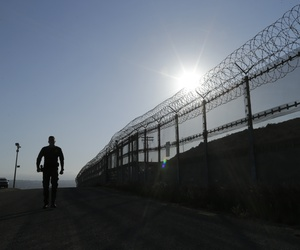 In this June 22, 2016, file photo, a Border Patrol agent walks along a border structure in San Diego, Calif.