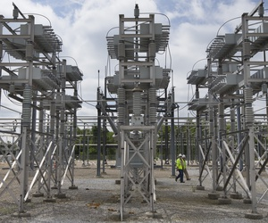In this Wednesday, May 20, 2015 photo, contractors walk past a capacitor bank at an AEP electrical transmission substation in Westerville, Ohio.