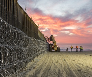 Border Patrol Agents at Border Field State Park in Imperial Beach watch over personnel that are reinforcing the border wall with concertina wire.