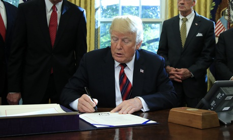 "President Donald Trump signs the ""America's Water Infrastructure Act of 2018"" into law during a ceremony in the Oval Office at the White House in Washington, Tuesday, Oct. 23, 2018."
