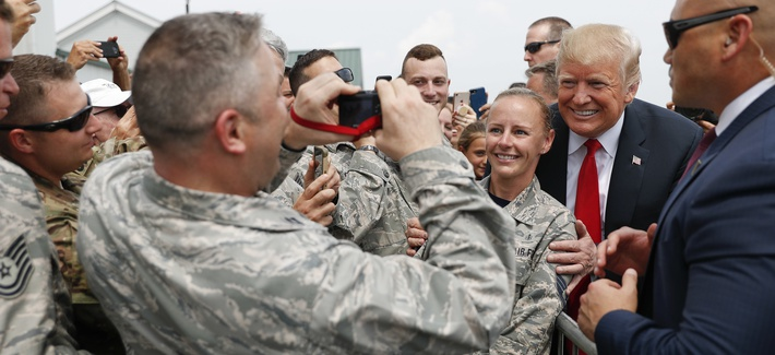 President Donald Trump poses for photographs while greeting members of the military on the tarmac upon his arrival on Air Force One at Francis S. Gabreski Airport in Westhampton, NY., Friday, Aug. 17, 2018.