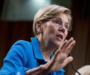 Sen. Elizabeth Warren, D-Mass., right, accompanied by Sen. Bernie Sanders, I-Vt., left, speaks during a news conference on Capitol Hill in Washington, Wednesday, Sept. 13, 2017.