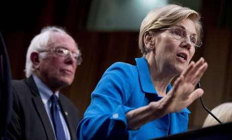 Sen. Elizabeth Warren, D-Mass., right, accompanied by Sen. Bernie Sanders, I-Vt., left, speaks during a news conference on Capitol Hill in Washington, Wednesday, Sept. 13, 2017.