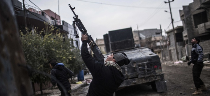 In this Sunday, Dec. 18, 2016 file photo, a member of the Iraqi Special Forces shoots his machine gun against an Islamic State militant drone n the al-Barid district in Mosul, Iraq.
