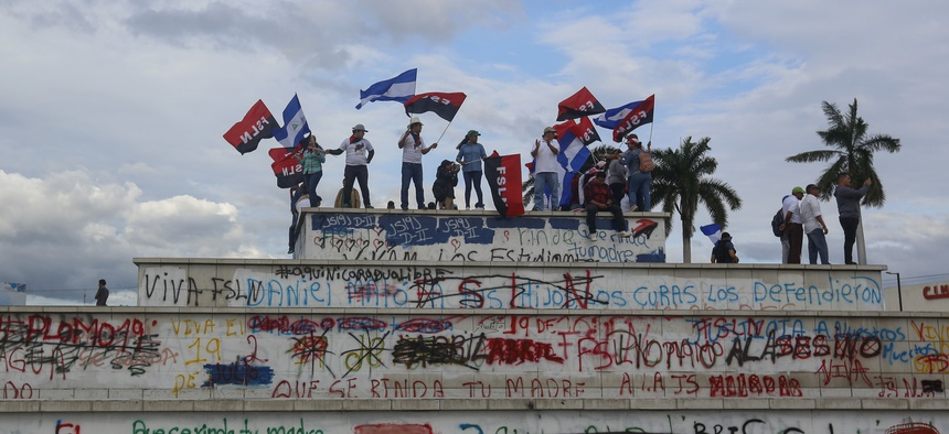 Government supporters wave Sandinista flags on top of the Metro Center roundabout during a pro-government march in Managua, Nicaragua, Wednesday, Sept. 26, 2018.