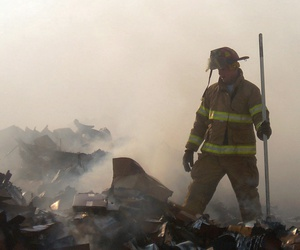 Two firefighters take a short break during a mop-up operation in a burn pit at a landfill on Forward Operating Base Speicher, near Tikrit, Iraq (IRQ), in support of Operation Iraqi Freedom.