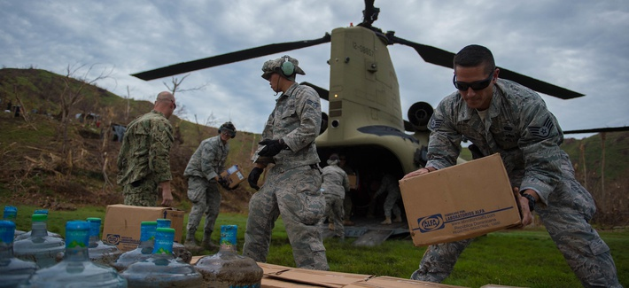 U.S. service members stack boxes of aid which and water while off loading a U.S. Army CH-47 Chinook during an aid relief mission Oct. 14, 2016, in Anse d'Hainault, Haiti.