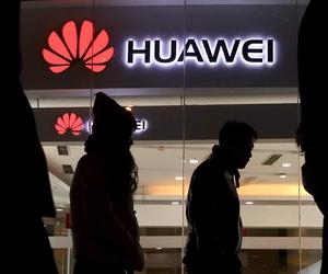 Pedestrians walk past a Huawei retail shop in Beijing Thursday, Dec. 6, 2018.