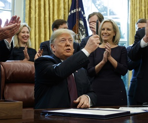 "President Donald Trump holds up a pen during a signing ceremony of the ""Cybersecurity and Infrastructure Security Agency Act,"" in the Oval Office of the White House, Friday, Nov. 16, 2018, in Washington."