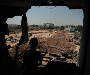 In this July 23, 2015 photo, a Palestinian boy looks from his family's house which was destroyed during the 2014 summer war between Israel and Hamas, as the long-awaited reconstruction began in Shijaiyah neighborhood eastern Gaza City.