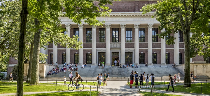 Panorama of the Harvard University's campus in Cambridge, MA, USA showcasing its historic architecture, gardens and students passing by on June 2, 2014.