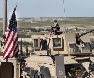 In this April 4, 2018 file photo, a U.S. soldier sits in an armored vehicle on a road leading to the tense front line with Turkish-backed fighters, in Manbij, north Syria.