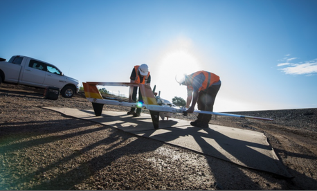 Brett Dokken and Stephen Marshall, unmanned aerial vehicle pilot contractors, prepare a civilian drone for takeoff at Melrose, New Mexico, Aug. 17, 2018.