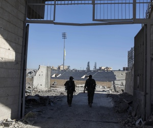 Members of the U.S.-backed Syrian Democratic Forces (SDF) enter the stadium that was the site of Islamic State fighters' last stand in the city of Raqqa, Syria, Wednesday, Oct. 18, 2017.