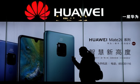A woman browses her smartphone as she walks by a Huawei store at a shopping mall in Beijing, Tuesday, Dec. 11, 2018.