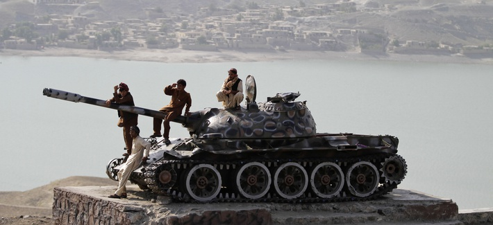 Afghan men sit on top of an old Soviet tank overlooking Naghlu lake on the outskirts of Kabul, Afghanistan, Thursday, Sept. 11, 2013.
