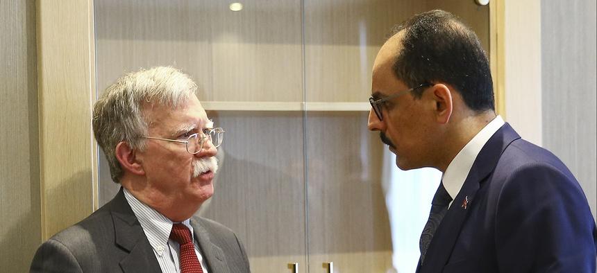 U.S. National Security Adviser John Bolton, left, and his Turkish counterpart and senior adviser to President Recep Tayyip Erdogan, Ibrahim Kalin, right, talk at the Presidential Palace in Ankara, Turkey, Tuesday, Jan. 8, 2019.