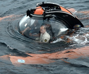 Russian President Vladimir Putin, center, sits on board a bathyscaphe as it plunges into the Black Sea along the coast of Sevastopol, Crimea, Tuesday, Aug. 18, 2015.