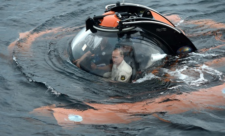 Russian President Vladimir Putin, center, sits on board a bathyscaphe as it plunges into the Black Sea along the coast of Sevastopol, Crimea, Tuesday, Aug. 18, 2015.