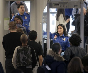 Transportation Security Administration agents help passengers through a security checkpoint at Newark Liberty International Airport in Newark, N.J., Monday, Jan. 7, 2019.