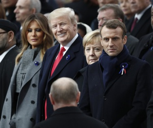 Russian President Vladimir Putin, back to camera, arrives to take his seat with French President Emmanuel Macron, Brigitte Macron, German Chancellor Angela Merkel, and U.S. President Donald Trump in Paris on Nov. 11, 2018.