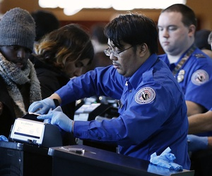 Transportation Security Administration officers check boarding passes and identification at Logan International Airport in Boston, Sunday, Dec. 23, 2018.