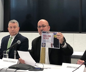 Thomas O'Connor (center), president of the FBI Agents Association, holds up a booklet with testimonials about the shutdown's impact.