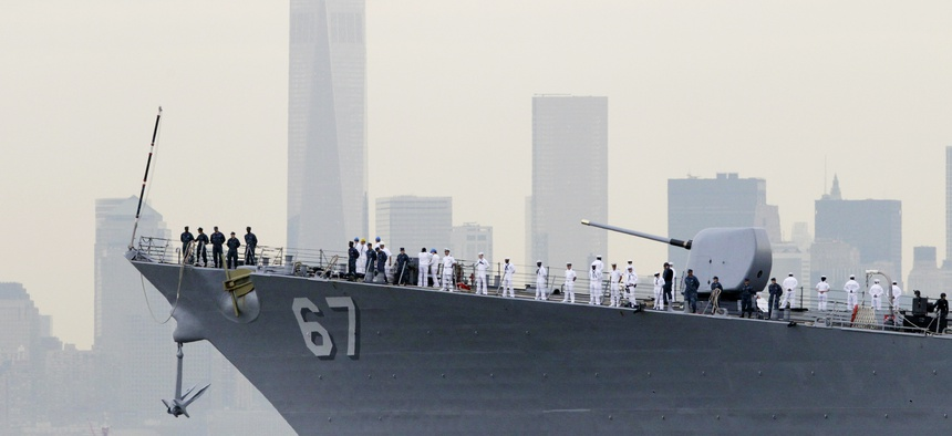 Sailors line the bow of the destroyer USS Cole as it glides past One World Trade Center and the lower Manhattan skyline, Wednesday, May 21, 2014 in New York.