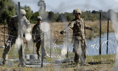 In this Nov. 16, 2018, photo, members of the U.S. military install multiple tiers of concertina wire along the banks of the Rio Grande near the Juarez-Lincoln Bridge at the U.S.-Mexico border in Laredo, Texas.