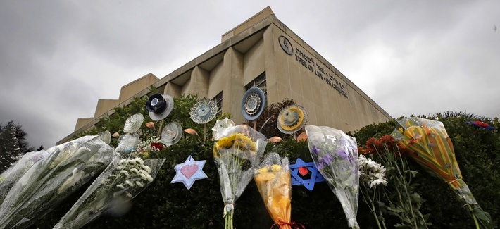 In this Tuesday, Nov. 20, 2018 photo, a makeshift memorial of flowers rests on bushes outside the Tree of Life Synagogue in Pittsburgh.