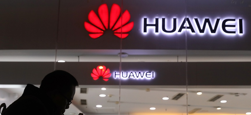 A man lights a cigarette outside a Huawei retail shop in Beijing Thursday, Dec. 6, 2018. China on Thursday demanded Canada release a Huawei Technologies executive who was arrested in a case that adds to technology tensions with Washington.