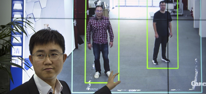 In this Oct. 31, 2018, photo, Huang Yongzhen, CEO of Watrix, demonstrates the use of his firm's gait recognition software at his company's offices in Beijing.