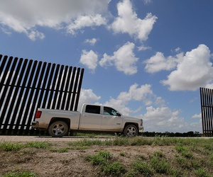 A farmer passes along a border fence that divides his property in Mission, Texas in 2015.