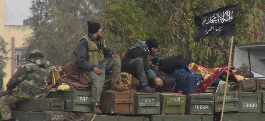 In this Friday, Jan. 11, 2013 file photo, rebels from al-Qaida-affiliated Jabhat al-Nusra, also known as the Nusra Front, sit on a truck full of ammunition at Taftanaz air base, that was captured by the rebels in Idlib province, northern Syria.