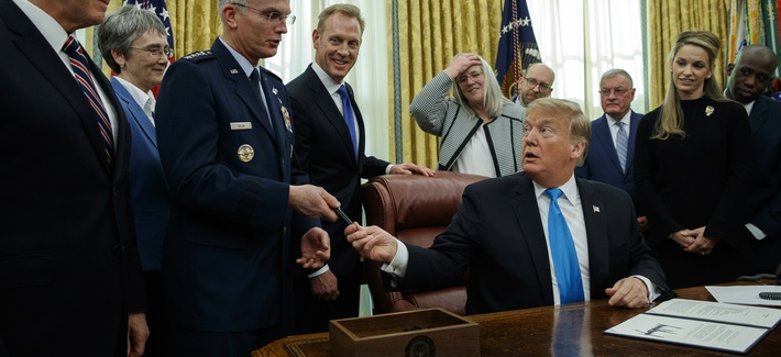 "President Donald Trump hands a pen to Air Force Gen. Paul Selva after signing ""Space Policy Directive 4"" in the Oval Office of the White House, Tuesday, Feb. 19, 2019, in Washington."