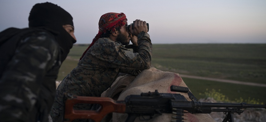 U.S.-backed Syrian Democratic Forces (SDF) fighters watch as an airstrike hits territory still held by Islamic State militants in the desert outside Baghouz, Syria, Tuesday, Feb. 19, 2019.