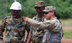 Sgt. Jose Portugal, a technical engineer assigned to Headquarters and Headquarters Company, 64th Engineer Battalion, 36th Engineer Brigade, discusses engineering methods with Ghanaian Army engineers at the Bundase Training Camp outside Accra, Ghana.
