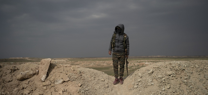 A U.S.-backed Syrian Democratic Forces, or SDF, fighter stands in the desert outside the village of Baghouz, Syria, Thurs., Feb. 14, 2019.