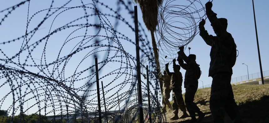 In this Nov. 16, 2018, file photo, members of the U.S. military install multiple tiers of concertina wire along the banks of the Rio Grande near the Juarez-Lincoln Bridge at the U.S.-Mexico border in Laredo, Texas.