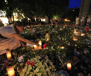 A woman lights candles among flowers and tributes laid outside the Oslo Cathedral in Oslo, Norway in memory of the victims of July 22 bomb attack and shooting rampage, late Sunday, July 31, 2011.